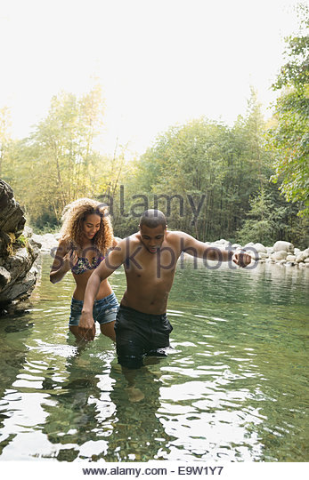 Couple at swimming hole in woods - Stock Image