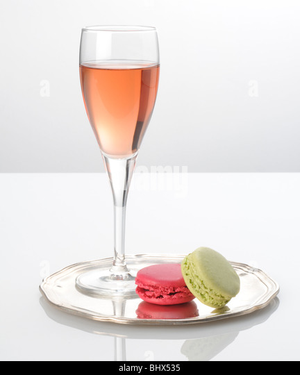 Pink champagne and macaroons on a silver tray - Stock Image