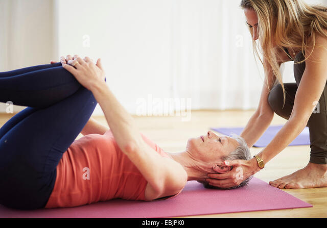 Mature female student lying on back holding knees in pilates class - Stock Image