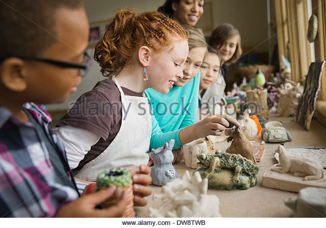 Friends displaying clay figurines in pottery class - Stock Image