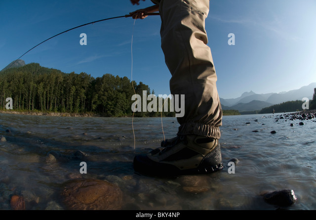 A man in waders casts into a river while fly fishing in Squamish, British Columbia. - Stock Image