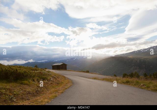 Sunlit rural road in mountain landscape, Jotunheimen National Park, Lom, Oppland, Norway - Stock Image