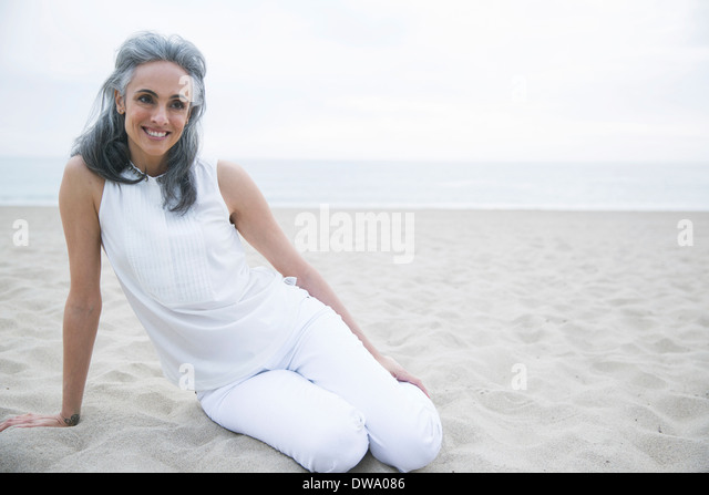 Mature woman relaxing on beach, Los Angeles, California, USA - Stock Image