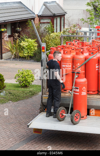 A delivery man delivering household red Calor Gas bottles on a pickup truck tail lift outside a domestic property. - Stock Image