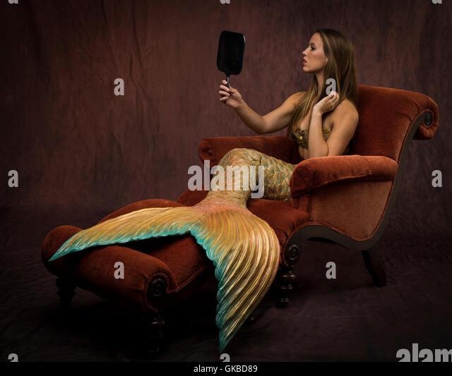 Mermaid sitting looking in a mirror - Stock Image