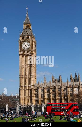 Tourists sitting on the grass of Parliament Square with Big Ben and the Houses of Parliament London. - Stock Image