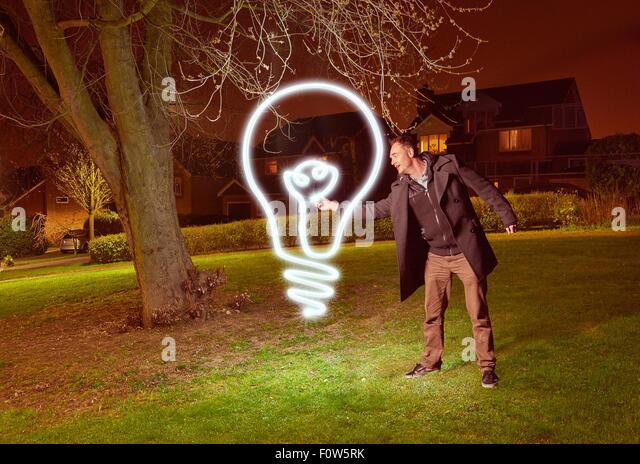 Artist light painting a lightbulb symbol in park - Stock Image