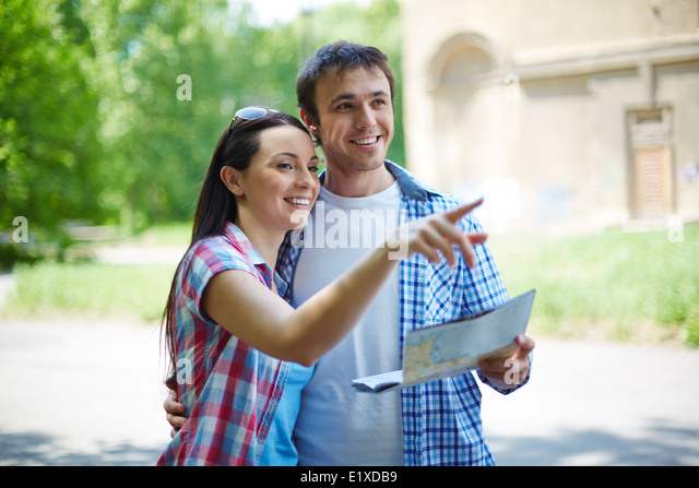 Portrait of pretty female explaining her husband sights of the city - Stock-Bilder