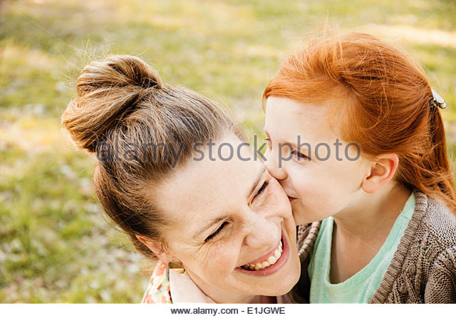 Portrait of smiling mid adult mother and daughter in park - Stock-Bilder