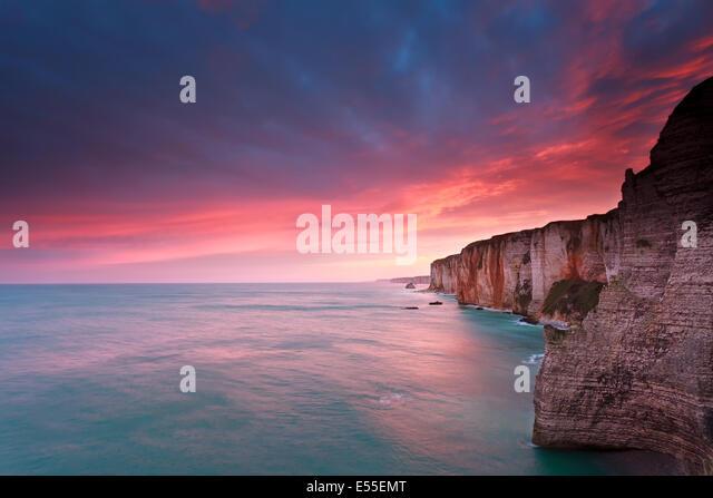 fire sunrise over cliffs in Atlantic ocean, France - Stock Image