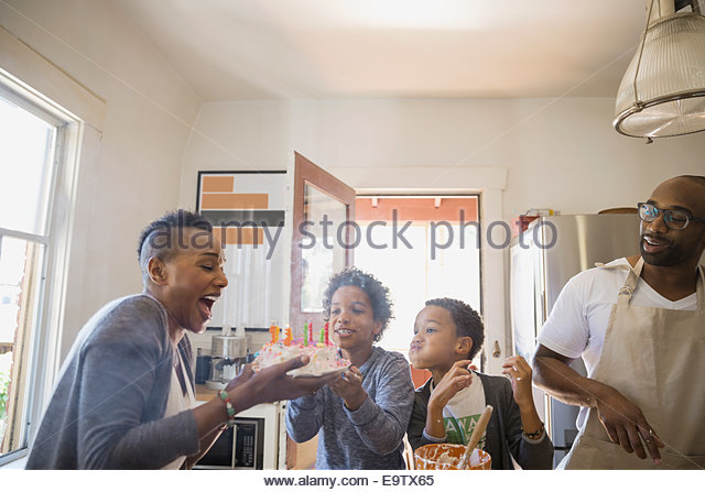 Family watching mother blow out birthday cake candles - Stock Image