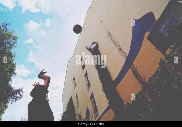 Low Angle View Of Man Playing Basketball Against Cloudy Sky - Stock Image