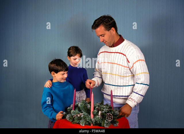 Father lights Advent candle in wreath as son and daughter stand next to him.Cutout.  MR ©Myrleen Pearson - Stock-Bilder