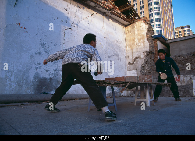Pingong Boys kids playing with a make shift ping pong table in a hutong in central Beijing - Stock Image