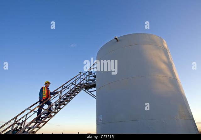 Oil industry worker on storage tank platform talking on phone. - Stock Image