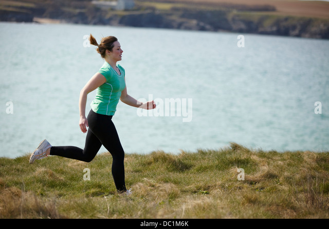 Young woman running near coast - Stock-Bilder