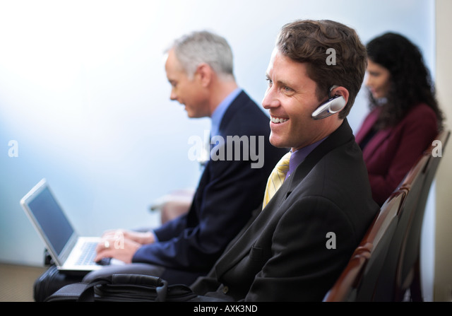 business job career men lady women male female waiting with technology phone computer communicating reading magazine - Stock Image