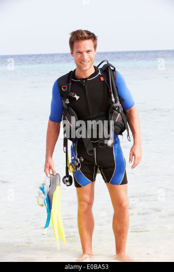 Man With Scuba Diving Equipment Enjoying Beach Holiday - Stock Image