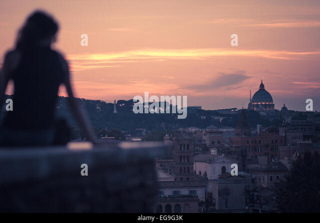Italy, Rome, Woman starring roman sunset at Giardino degli Aranci Peak - Stock Image