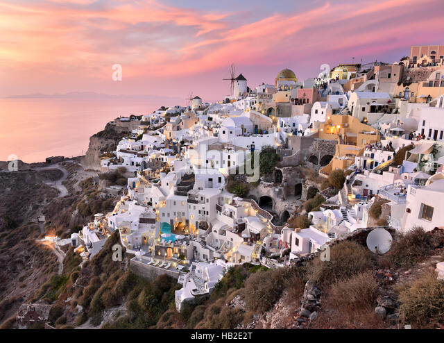 Oia Village in Cycladic Architecture style in Santorini, Greece during a pink sunset. - Stock Image