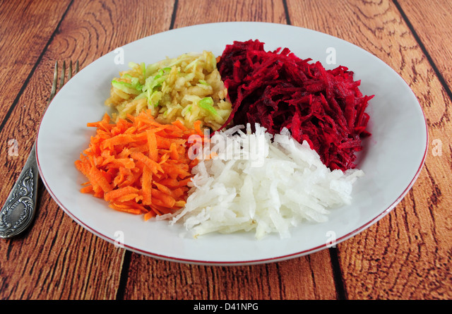 Salad from shredded beetroot, turnip, carrot and apple in a plate - Stock Image