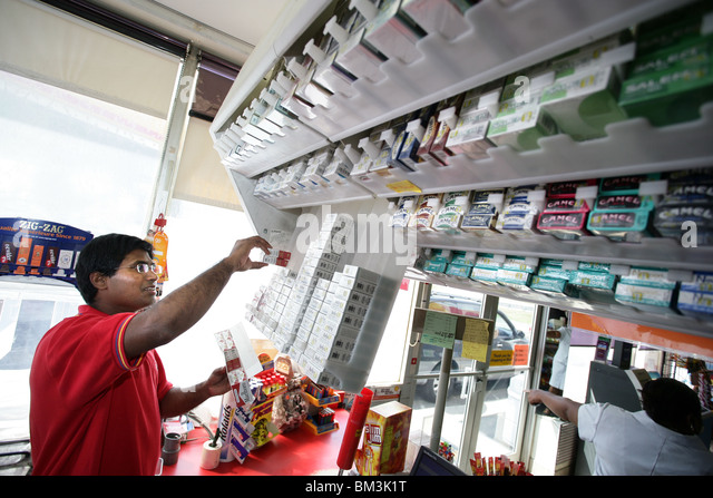 A convenience store clerk at a gas station fills cigarette holders behind the counter. Prices have risen again due - Stock Image