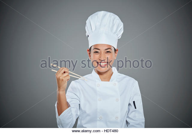 Portrait of young chef holding chopsticks. - Stock Image