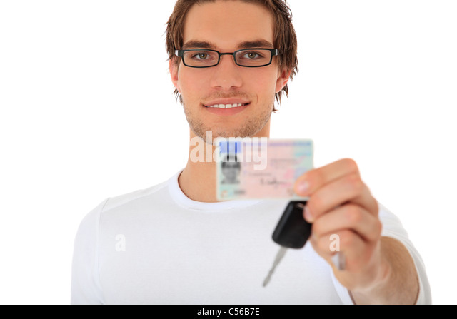 Young guy showing his drivers license and car keys. Selective focus on person in background. License details are - Stock Image