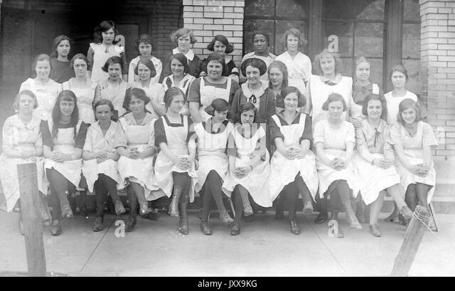 Full length portrait of a group of schoolgirls, first row seated, second and third rows standing, all girls wearing - Stock Image
