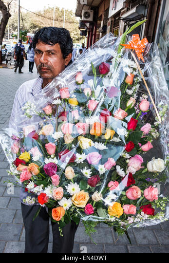 India Asian Mumbai Churchgate Veer Nariman Road man delivering wreath rose roses flowers - Stock Image