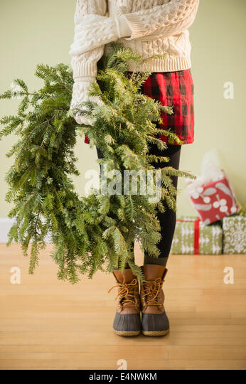 Low section of woman holding christmas wreath - Stock Image