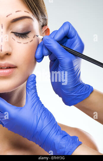 Beautiful woman half face photo plastic surgery, plastic surgeon hands - Stock-Bilder
