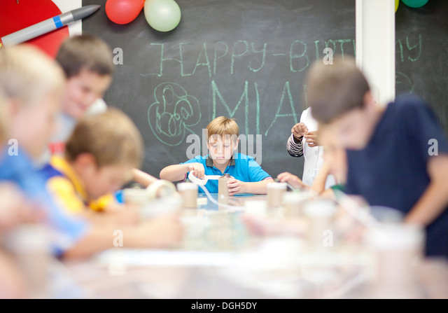 Boys making objects at children's birthday party - Stock Image