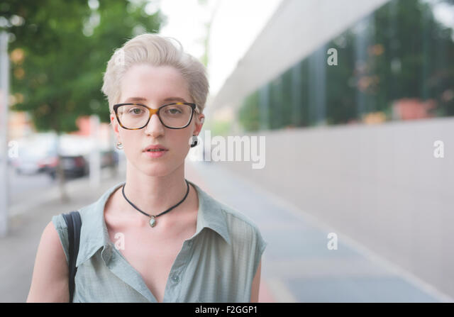 Portrait of a young handsome caucasian blonde italian designer posing in the city, looking in camera, serious - - Stock Image