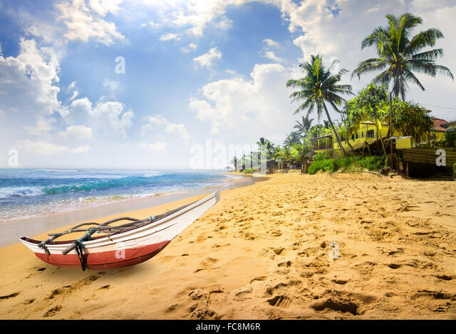 Small boat on a beach of the ocean in Sri Lanka - Stock Image