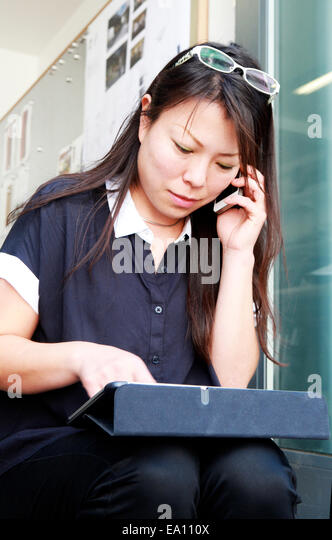 Female architect using smartphone and digital tablet on office step - Stock Image