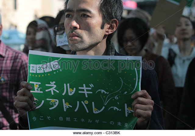 A man holds up a sign calling for sustainable energy solutions as 5,000 activists march through Shibuya, Tokyo. - Stock Image
