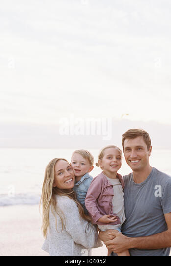 Couple standing with their son and daughter on a sandy beach by the ocean, looking at camera, smiling. - Stock Image