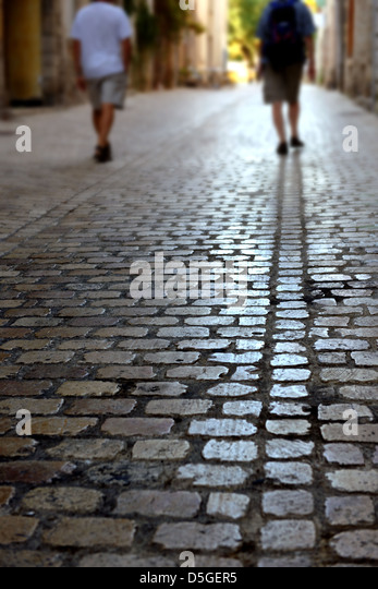 Two people walking down a cobbled street in France - Stock Image