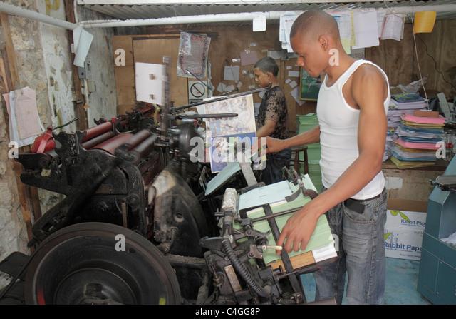 Santo Domingo Dominican Republic Ciudad Colonia Calle Isabel la Catolica Black man teen labor job print shop business - Stock Image