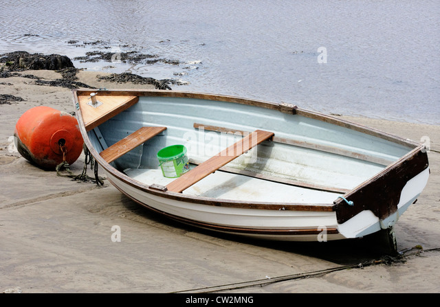A small rowing boat beached on the tide line. - Stock Image