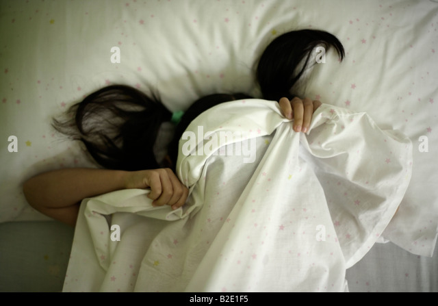Five year old girl hides beneath sheets after tantrum - Stock Image