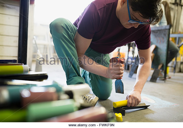 Glassblower cutting yellow clay in workshop - Stock Image