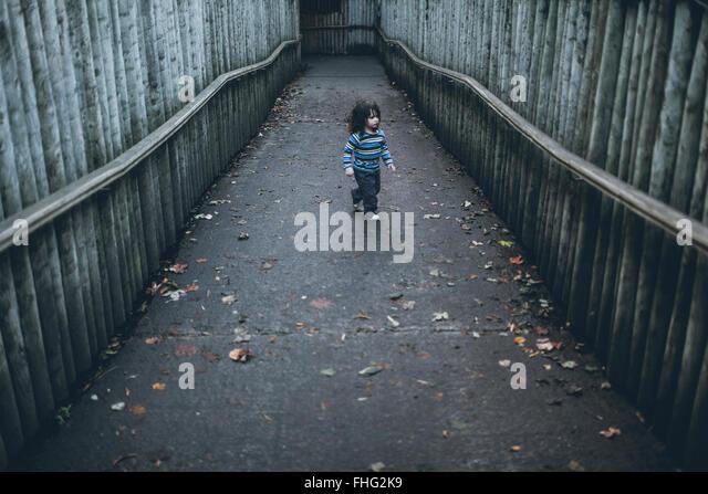 Boy walking on path between high wooden poles - Stock Image