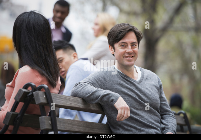 View over citySitting on a park bench A man smiling at the camera Four people in the background - Stock Image
