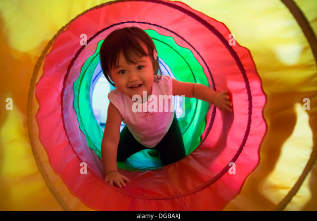 Baby girl crawling through play tunnel - Stock Image