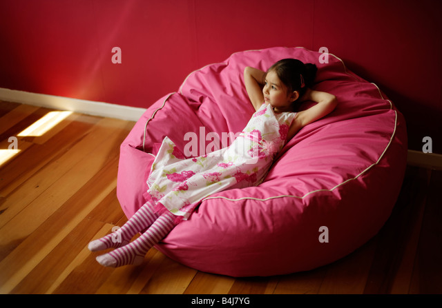 Girl 5 relaxes on pink bean bag - Stock Image