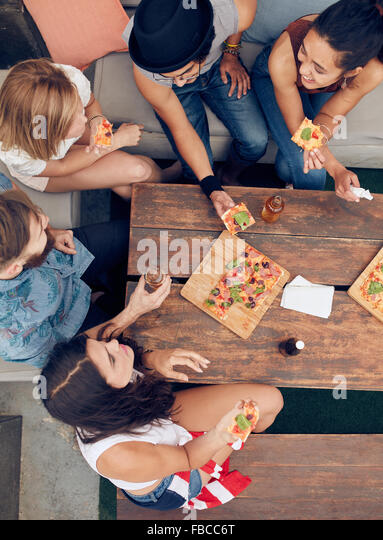 Top view of group of young people having drinks and pizza at party. Multiracial friends hanging out together. - Stock Image