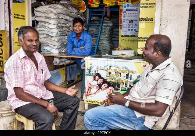 India Asian Mumbai Dharavi 60 Feet Road small business cement mix sale man owner friends - Stock Image