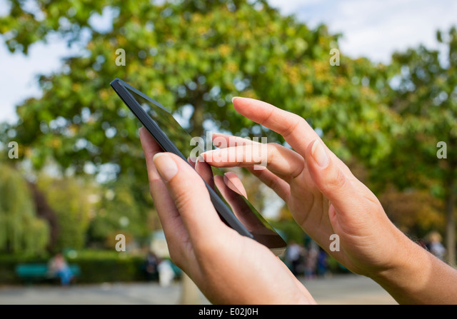 close-up Female mobile phone Trees Bench outdoor message sms e-mail - Stock Image
